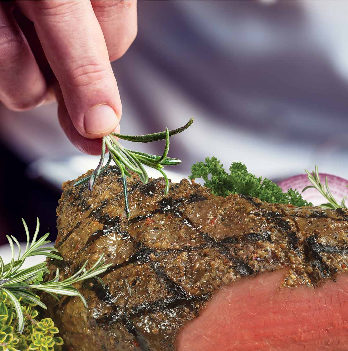 Closeup of Chef's fingers garnishing beef