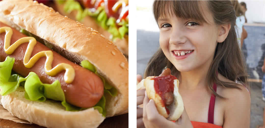 Young girl eating hotdog
